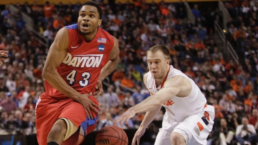 Syracuse's Trevor Cooney (10) knocks the ball away from Dayton's Vee Sanford (43) during the first half of a third-round game in the NCAA men's college basketball tournament in Buffalo, N.Y., Saturday, March 22, 2014. (AP Photo/Bill Wippert)
