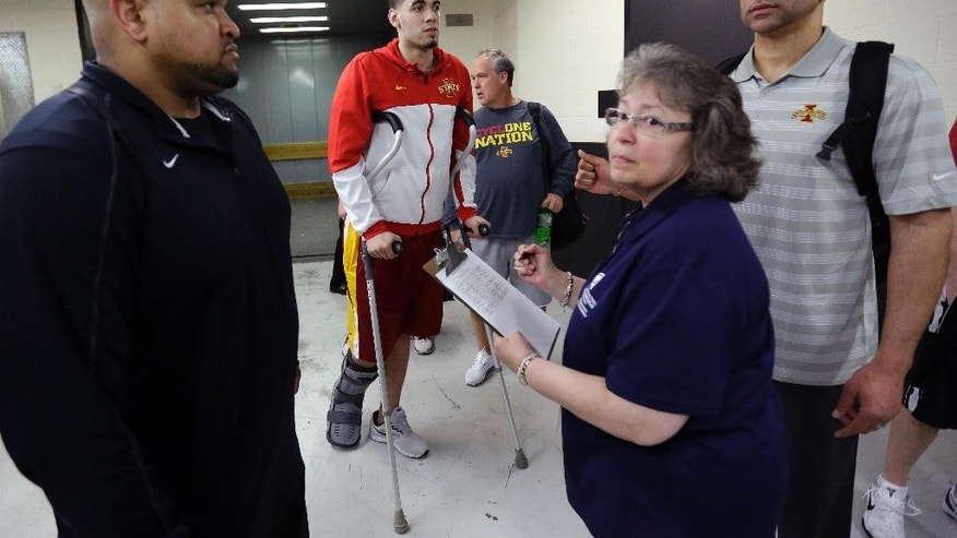 Iowa State's Georges Niang, center, checks in through security for the team's practice for the NCAA men's college basketball tournament, Saturday, March 22, 2014, in San Antonio. Niang broke his foot during a game Friday night and will not play when Iowa State faces North Carolina on Sunday. (AP Photo/Eric Gay)