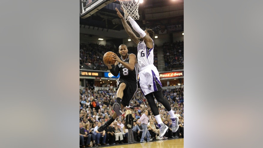 San Antonio Spurs guard Patty Mills, left,  of Australia, is fouled as he drives to the basket past Sacramento Kings Ben McLemore during the first quarter of an NBA basketball game in Sacramento, Calif., Friday, March 21, 2014.(AP Photo/Rich Pedroncelli)