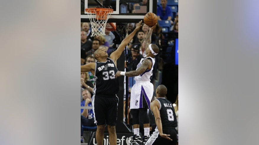 San Antonio Spurs forward Boris Diaw, left, of France, tries to block the shot of Sacramento Kings guard Isaiah Thomas during the first quarter of an NBA basketball game in Sacramento, Calif., Friday, March 21, 2014.(AP Photo/Rich Pedroncelli)