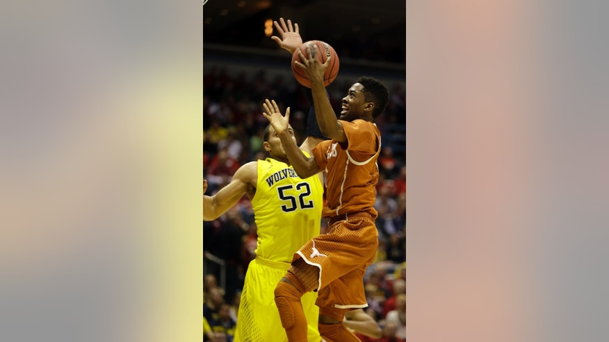 Texas guard Isaiah Taylor (1) goes to the basket against Michigan forward Jordan Morgan (52) during the first half of a third-round game of the NCAA college basketball tournament Saturday, March 22, 2014, in Milwaukee. (AP Photo/Jeffrey Phelps)