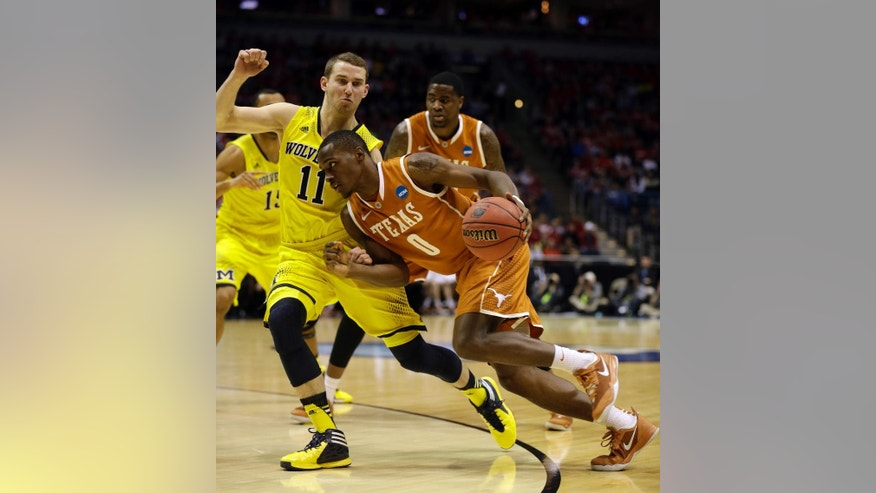 Texas guard Kendal Yancy (0) drives the ball against Michigan guard Nik Stauskas (11) during the first half of a third-round game of the NCAA college basketball tournament Saturday, March 22, 2014, in Milwaukee. (AP Photo/Jeffrey Phelps)