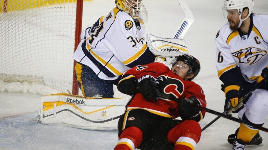 Nashville Predators goalie Carter Hutton, left, and teammate Shea Weber watch as Calgary Flames' Jiri Hudler, from the Czech Republic, chases the puck during the third period of an NHL hockey game in Calgary, Alberta, Friday, March 21, 2014. The Predators won 6-5. (AP Photo/The Canadian Press, Jeff McIntosh)