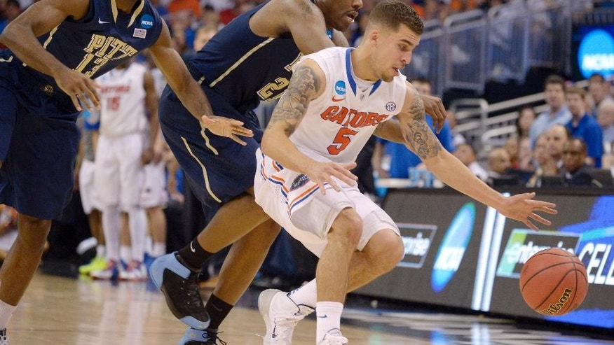 Florida guard Scottie Wilbekin (5) forces Pittsburgh forward Lamar Patterson (21) to turnover the ball as Pittsburgh guard Josh Newkirk (13) closes in during the second half in a third-round game in the NCAA college basketball tournament  Saturday, March 22, 2014, in Orlando, Fla. (AP Photo/Phelan M. Ebenhack)