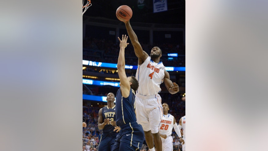 Florida center Patric Young (4) blocks a shot by Pittsburgh guard James Robinson (0) during the second half in a third-round game in the NCAA college basketball tournament  Saturday, March 22, 2014, in Orlando, Fla. (AP Photo/Phelan M. Ebenhack)
