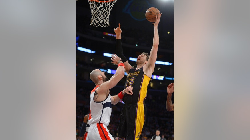 Los Angeles Lakers center Pau Gasol, right, of Spain, shoots as Washington Wizards center Marcin Gortat, of Poland, defends during the first half of an NBA basketball game, Friday, March 21, 2014, in Los Angeles. (AP Photo/Mark J. Terrill)