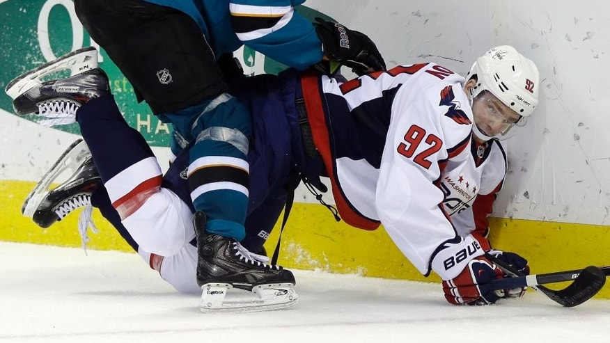 Washington Capitals' Evgeny Kuznetsov (92), of Russia, is pressed against the boards by San Jose Sharks' Jason Demers during the second period of an NHL hockey game Saturday, March 22, 2014, in San Jose, Calif. (AP Photo/Marcio Jose Sanchez)