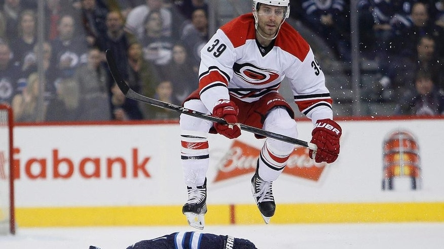 Carolina Hurricanes' Patrick Dwyer (39) leaps over Winnipeg Jets' Matt Halischuk (15) during the second period of an NHL hockey game, Saturday, March 22, 2014, in Winnipeg, Manitoba. (AP Photo/The Canadian Press, John Woods)