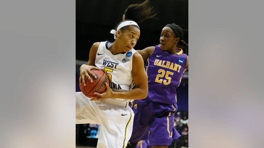 West Virginia forward Averee Fields (5) looks for an open teammate after pulling down a rebound past the defense of Albany forward Shereesha Richards (25) in the first half of an NCAA college basketball first-round tournament game on Sunday, March 23, 2014, in Baton Rouge, La. (AP Photo/Rogelio V. Solis)