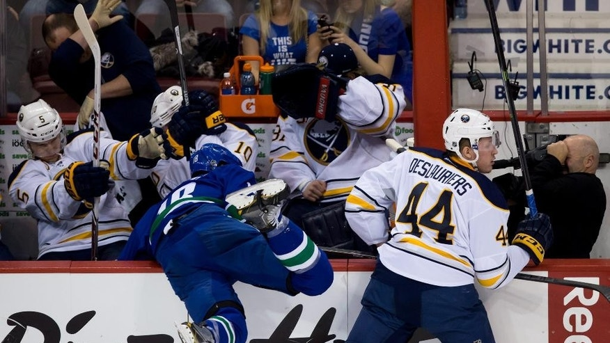 Buffalo Sabres' Nicolas Deslauriers, right, checks Vancouver Canucks' Ryan Stanton, left, into the Sabres' bench as, from left, Chad Ruhwedel,  Christian Ehrhoff, of Germany, and goalie Matt Hackett get out of the way during second period NHL hockey action in Vancouver, British Columbia, on Sunday March 23, 2014. (AP Photo/The Canadian Press, Darryl Dyck)