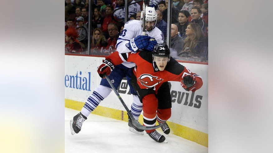 New Jersey Devils' Jon Merrill (34) is hit by Toronto Maple Leafs' Nazem Kadri (43) during the first period of an NHL hockey game, Sunday, March 23, 2014, in Newark, N.J. (AP Photo/Mel Evans)