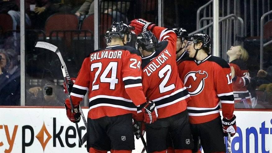 New Jersey Devils players swarm on Damien Brunner, of the Czech Republic, after he scored a goal during the first period of an NHL hockey game against the Toronto Maple Leafs, Sunday, March 23, 2014, in Newark, N.J. (AP Photo/Mel Evans)