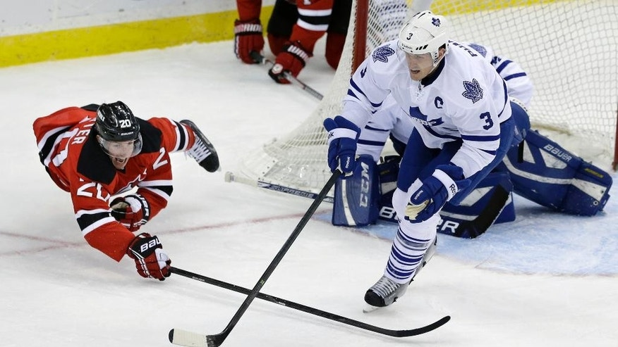 New Jersey Devils' Ryan Carter (20) dives for the puck with Toronto Maple Leafs' Dion Phaneuf (3) during the second period of an NHL hockey game, Sunday, March 23, 2014, in Newark, N.J. (AP Photo/Mel Evans)