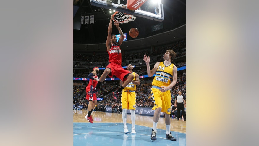 Washington Wizards forward Trevor Ariza, left, hangs from the rim after dunking as Denver Nuggets forwards Darrell Arthur, center, and Jan Vesely, of the Czech Republic, look on in the first quarter of an NBA basketball game in Denver on Sunday, March 23, 2014. (AP Photo/David Zalubowski)