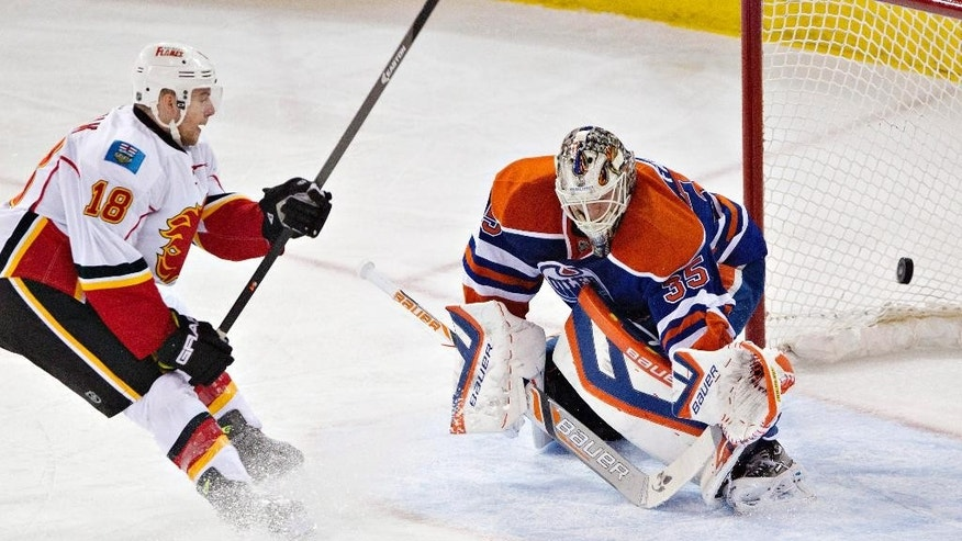 Calgary Flames' Matt Stajan (18) scores a goal against Edmonton Oilers goalie Viktor Fasth (35) during the second period of an NHL hockey game Saturday, March 22, 2014, in Edmonton, Alberta. (AP Photo/The Canadian Press, Jason Franson)
