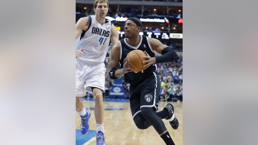 Brooklyn Nets forward Paul Pierce (34) drives past Dallas Mavericks forward Dirk Nowitzki (41) of Germany during the first half of an NBA basketball game Sunday, March 23, 2014, in Dallas. (AP Photo/LM Otero)