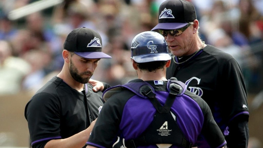 Colorado Rockies starting pitcher Tyler Chatwood, left, talks with pitching coach Jim Wright, right, as catcher Michael McKenry looks on during the second inning of a spring exhibition baseball game against the Chicago White Sox in Scottsdale, Ariz., Sunday, March 23, 2014. (AP Photo/Chris Carlson)