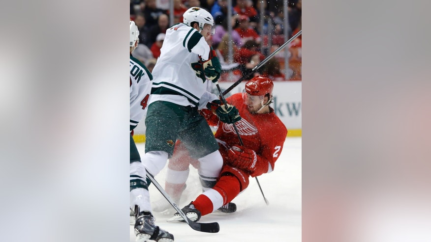 Minnesota Wilds' Ryan Suter, left, knocks Detroit Red Wings' Brendan Smith (2) off the puck during the second period of an NHL hockey game Sunday, March 23, 2014 in Detroit. (AP Photo/Duane Burleson)