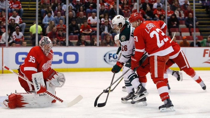 Minnesota Wilds' Matt Moulson (26) loses the puck against Detroit Red Wings' Brian Lashoff (23) while skating on Detroit Red Wings goalie Jimmy Howard (35) during the first period of an NHL hockey game Sunday, March 23, 2014 in Detroit. (AP Photo/Duane Burleson)