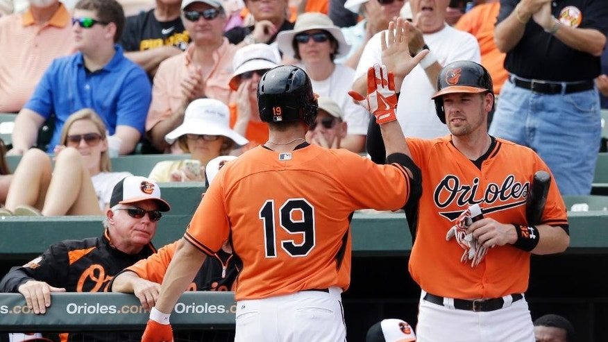 Baltimore Orioles' Chris Davis (19) is greeted at the dugout after his solo home run during the third inning of a spring exhibition baseball game against the Pittsburgh Pirates in Sarasota, Fla., Sunday, March 23, 2014. (AP Photo/Carlos Osorio)