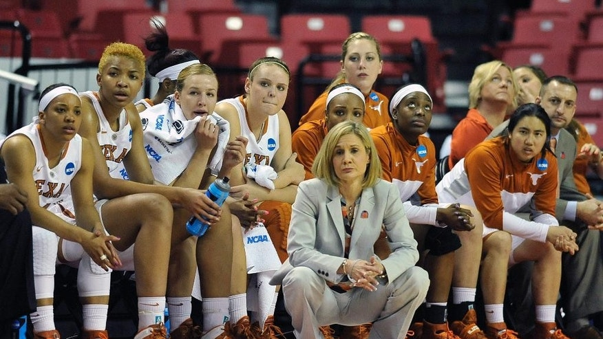 Texas head coach Karen Aston, front, and her team look on during the first half of the first round of the NCAA women's college basketball tournament game against Penn, Sunday, March 23, 2014, in College Park, Md. (AP Photo/Gail Burton)