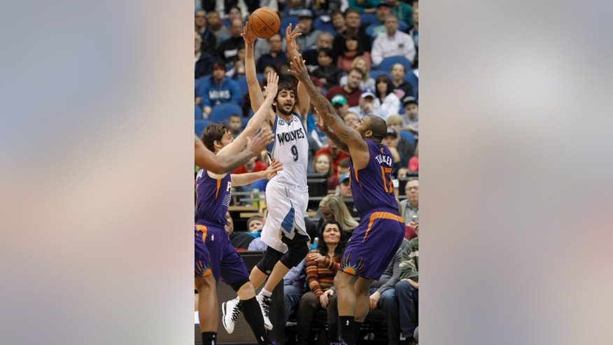 Minnesota Timberwolves guard Ricky Rubio (9), of Spain, passes under pressure from Phoenix Suns guard Goran Dragic, left, of Slovenia, and Phoenix Suns forward P.J. Tucker (17) during the first quarter of an NBA basketball game in Minneapolis, Sunday, March 23, 2014. (AP Photo/Ann Heisenfelt)