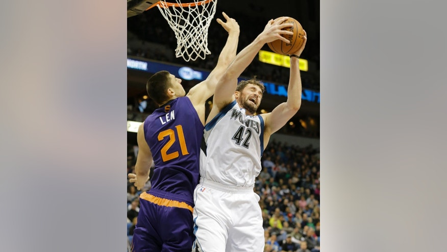 Minnesota Timberwolves forward Kevin Love (42) pulls down a rebound against Phoenix Suns center Alex Len (21), of Ukraine, during the second quarter of an NBA basketball game in Minneapolis, Sunday, March 23, 2014. (AP Photo/Ann Heisenfelt)