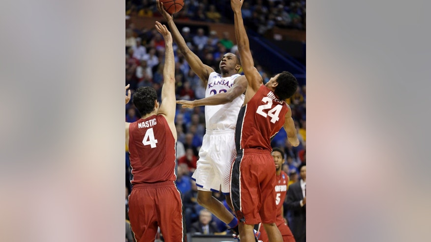 Kansas' Andrew Wiggins, center, heads to the basket past Stanford's Stefan Nastic, left, and Josh Huestis during the first half of a third-round game of the NCAA college basketball tournament Sunday, March 23, 2014, in St. Louis. (AP Photo/Jeff Roberson)