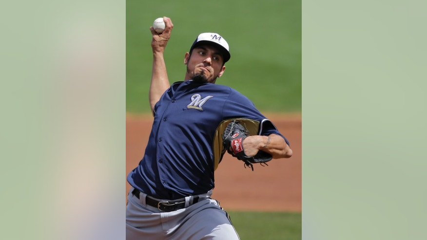 Milwaukee Brewers starting pitcher Matt Garza delivers against the Cincinnati Reds in the first inning of a spring exhibition baseball game Sunday, March 23, 2014, in Goodyear, Ariz. (AP Photo/Mark Duncan)