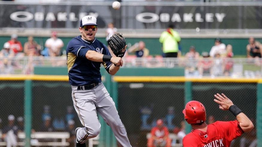 Milwaukee Brewers second baseman Scooter Gennett, left, throws over Cincinnati Reds' Ryan Ludwick (48) to complete a double play on Reds' Todd Frazier in the second inning of a spring exhibition baseball game Sunday, March 23, 2014, in Goodyear, Ariz. (AP Photo/Mark Duncan)
