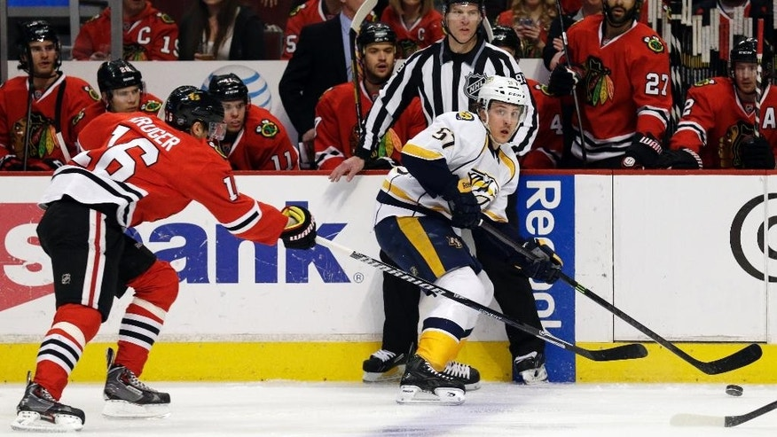 Nashville Predators' Gabriel Bourque (57), right, looks to a pass against Chicago Blackhawks' Marcus Kruger (16)  during the first period of an NHL hockey game in Chicago, Sunday, March 23, 2014. (AP Photo/Nam Y. Huh)