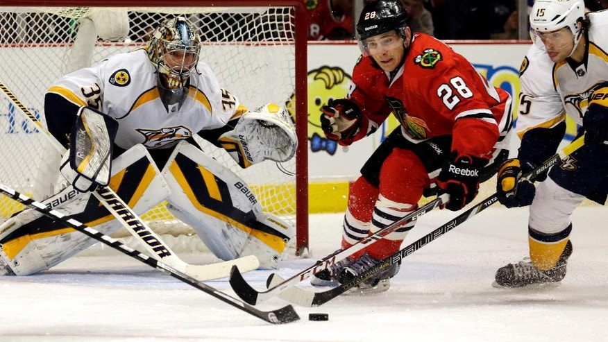 Chicago Blackhawks' Ben Smith (28) battles for the puck against Nashville Predators' Craig Smith (15) as  goalie Pekka Rinne (35) looks on during the second period of an NHL hockey game in Chicago, Sunday, March 23, 2014. (AP Photo/Nam Y. Huh)