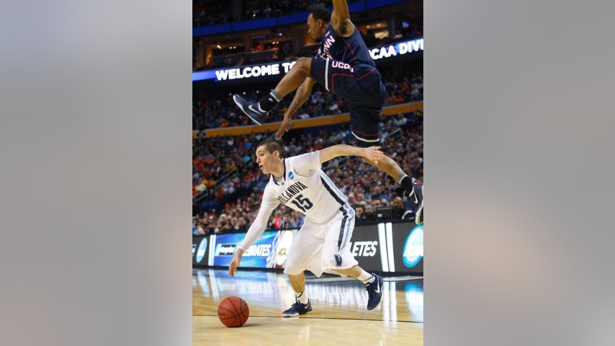 Villanova's Ryan Arcidiacono (15) drives under Connecticut's Ryan Boatright during the first half of a third-round game in the NCAA men's college basketball tournament in Buffalo, N.Y., Saturday, March 22, 2014. (AP Photo/Bill Wippert)