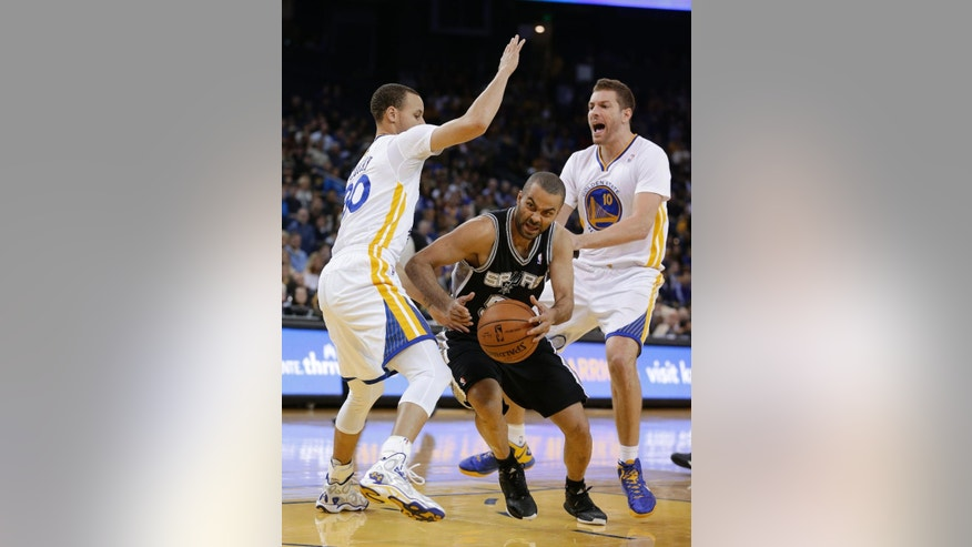 San Antonio Spurs guard Tony Parker drives to the basket between Golden State Warriors guard Stephen Curry, left, and forward David Lee during the first quarter of an NBA basketball game Saturday, March 22, 2014, in Oakland, Calif. (AP Photo/Eric Risberg)