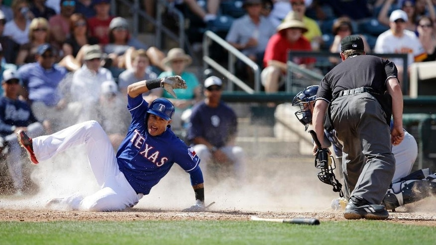 Texas Rangers' Leonys Martin, left, slides safe at home as San Diego Padres catcher Yasmani Grandal and umpire Allen Bailey watch during the third inning of a spring exhibition baseball game Sunday, March 23, 2014, in Surprise, Ariz. Martin was originally called out but the was call was reversed after being reviewed. (AP Photo/Darron Cummings)