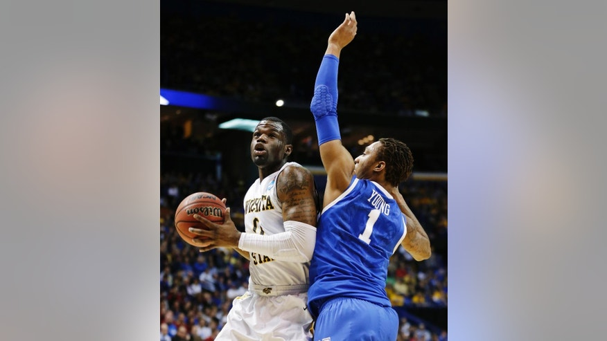 Wichita State  forward Chadrack Lufile (0) is defended by Kentucky guard/forward James Young (1) during the first half of a third-round game of the NCAA college basketball tournament Sunday, March 23, 2014, in St. Louis. (AP Photo/Charlie Riedel)