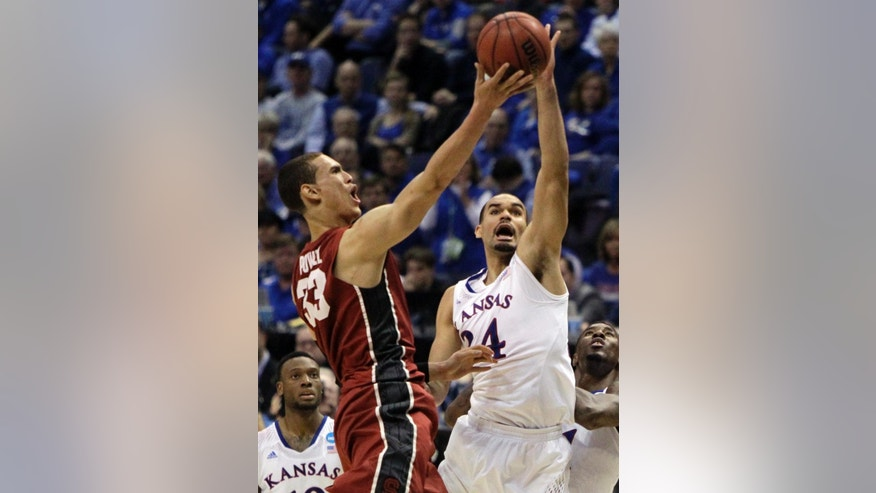 Stanford's Dwight Powell, left, heads to the basket as Kansas' Perry Ellis defends during the second half of a third-round game of the NCAA college basketball tournament Sunday, March 23, 2014, in St. Louis. Stanford won 60-57. (AP Photo/Jeff Roberson)