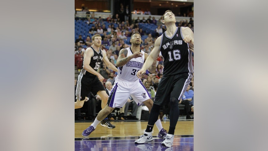 In this photo taken Friday, March 21, 2014, Sacramento Kings forward Royce White center, playing in his first NBA basketball game, positions himself for a rebound, between San Antonio Spurs' Matt Bonner, left, and Aron Baynes, of Australia, in Sacramento, Calif.,  White was drafted by the Houston Rockets with the No. 16 pick in the 2012 draft but spent his rookie season in a dispute with the team over how to treat his anxiety disorder which includes a fear of flying. Not only must he prove he can still play, White, who is on his second 10 day contract with the Kings, has to show he can handle the rigors of the league's schedule including his first road trip this week.(AP Photo/Rich Pedroncelli)
