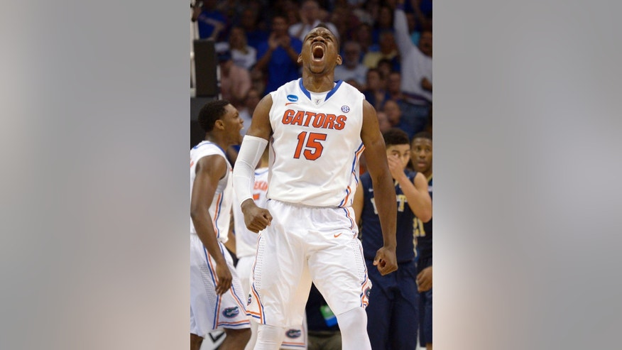 Florida forward Will Yeguete (15) yells after scoring against Pittsburgh during the second half in a third-round game in the NCAA college basketball tournament  Saturday, March 22, 2014, in Orlando, Fla. (AP Photo/Phelan M. Ebenhack)