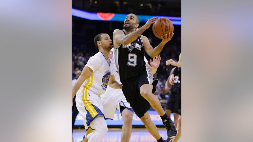 San Antonio Spurs guard Tony Parker, right, goes to the basket and scores as Golden State Warriors guard Stephen Curry, left, looks on during the first quarter of their NBA basketball game Saturday, March 22, 2014, in Oakland, Calif. San Antonio won the game 99-90. (AP Photo/Eric Risberg)