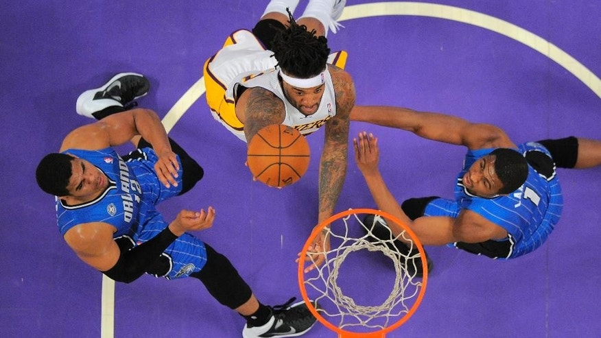 Los Angeles Lakers forward Jordan Hill, center, puts up a shot as Orlando Magic forward Tobias Harris, left, and guard Doron Lamb defend during the first half of an NBA basketball game, Sunday, March 23, 2014, in Los Angeles.  (AP Photo/Mark J. Terrill)