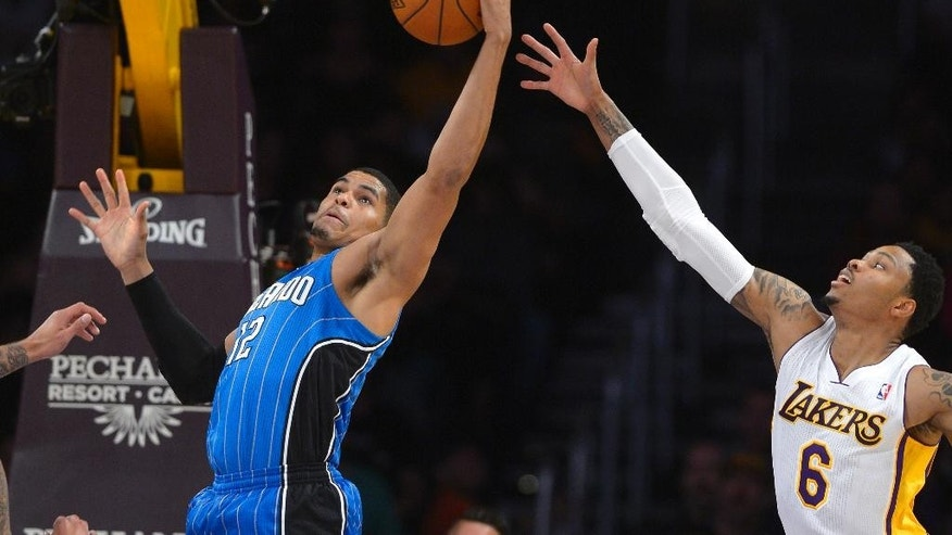 Orlando Magic forward Tobias Harris, left, grabs a rebound away from Los Angeles Lakers guard Kent Bazemore during the first half of an NBA basketball game, Sunday, March 23, 2014, in Los Angeles.  (AP Photo/Mark J. Terrill)