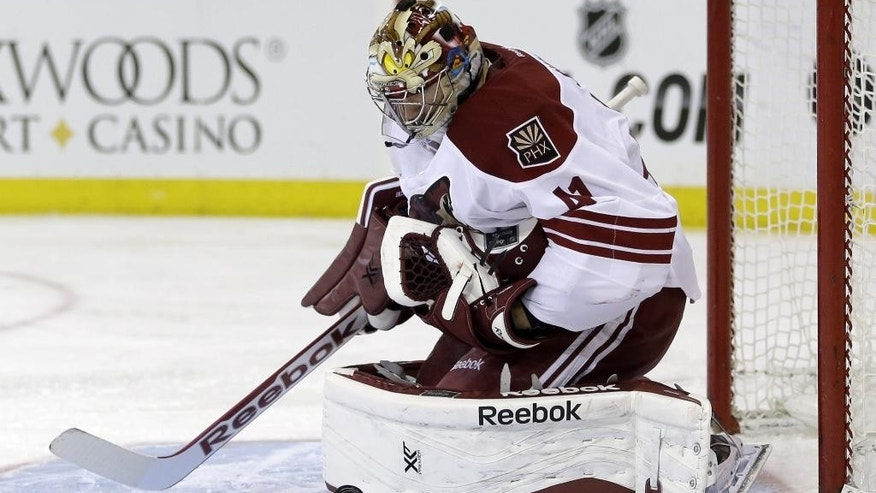 Phoenix Coyotes goalie Mike Smith makes a save during the second period of the NHL hockey game against the New York Rangers, Monday, March 24, 2014, in New York. (AP Photo/Seth Wenig)