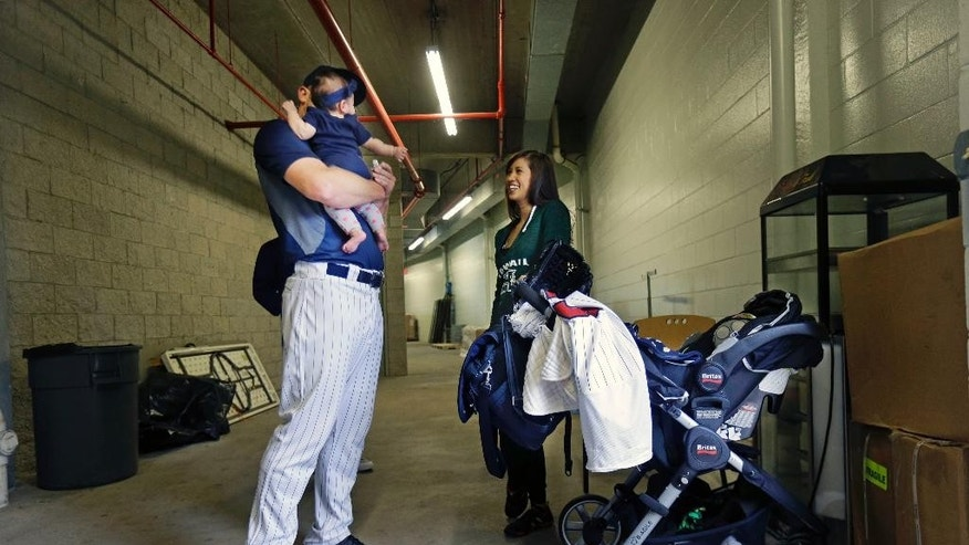 Minnesota Twins relief pitcher Casey Fien holds his five-month old baby, Jordan, with his wife Joann, in the players tunnel in Hammond Stadium, during a rain delay before an exhibition baseball game against the Tampa Bay Rays in Fort Myers, Fla., Monday, March 24, 2014. The game was later canceled due to inclement weather. (AP Photo/Gerald Herbert)