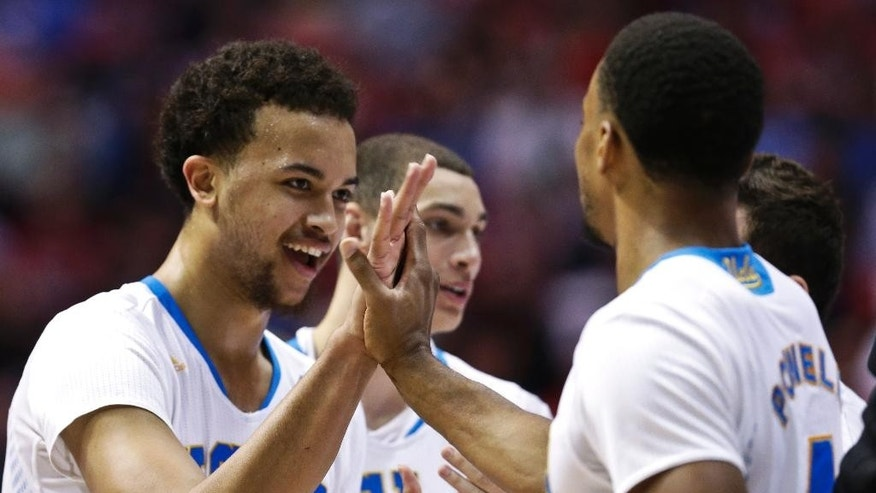 UCLA 's Kyle Anderson and Norman Powell, right, celebrate during the second half of a third-round victory over Stephen F. Austin in the NCAA college basketball tournament, Sunday, March 23, 2014, in San Diego. (AP Photo/Gregory Bull)