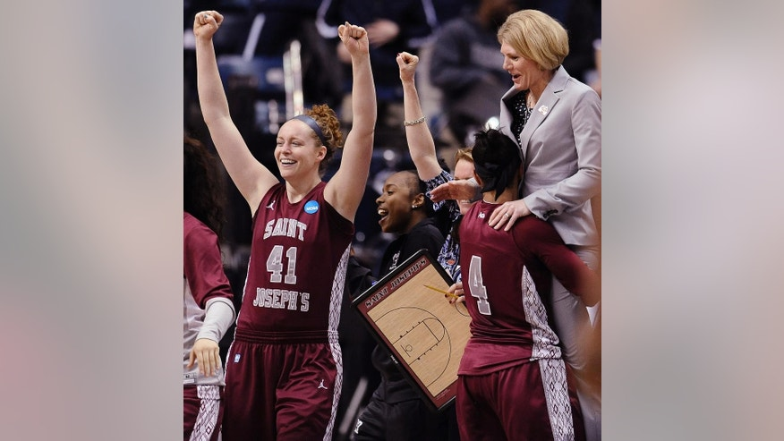 Saint Joseph's Sarah Fairbanks (41) and Natasha Cloud (4), and head coach Cindy Griffin, right, celebrate at the end of the second half of a first-round game of the NCAA women's college basketball tournament, Sunday, March 23, 2014, in Storrs, Conn. Saint Joseph's won 67-57 over Georgia. (AP Photo/Jessica Hill)