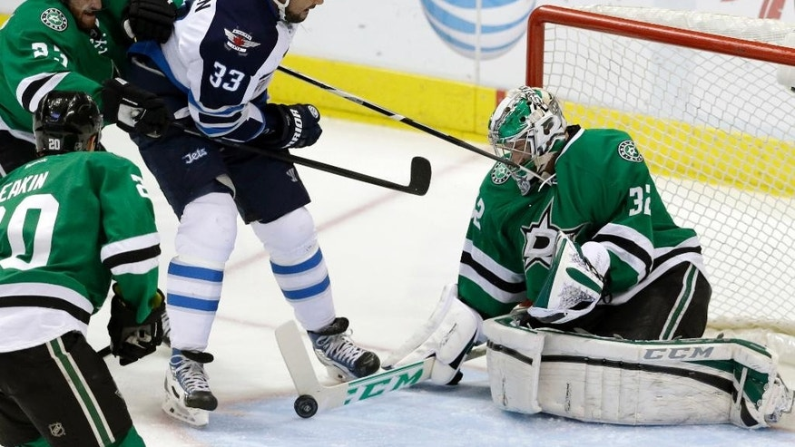 Winnipeg Jets defenseman Dustin Byfuglien (33) tries to score against Dallas Stars goalie Kari Lehtonen (32), defenseman Kevin Connauton (23) and center Shawn Horcoff (10) during the first period of an NHL hockey game, Monday, March 24, 2014, in Dallas. (AP Photo/LM Otero)