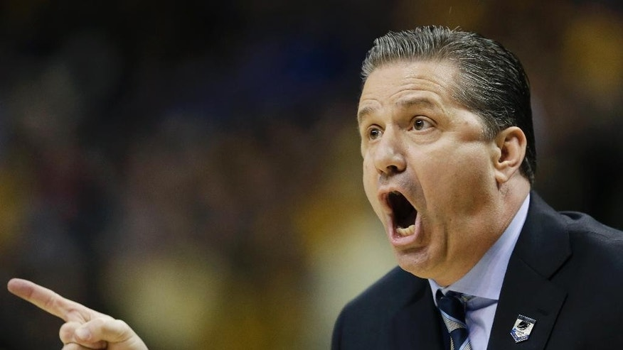 Kentucky head coach John Calipari works from the sideline against Wichita State  during the first half of a third-round game of the NCAA college basketball tournament Sunday, March 23, 2014, in St. Louis. (AP Photo/Charlie Riedel)