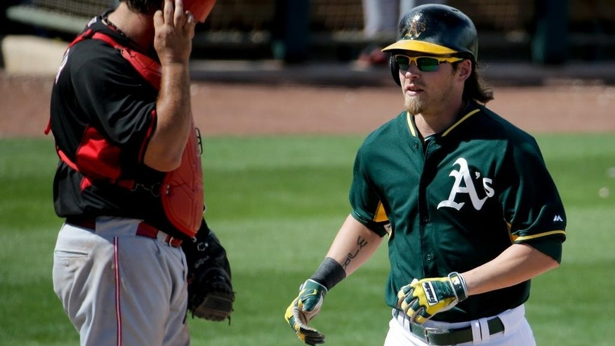 Oakland Athletics' Josh Reddick, scores past Cincinnati Reds catcher Cory Miller after a home run during the fifwbbth inning of a spring exhibition baseball game in Phoenix, Tuesday, March 25, 2014. (AP Photo/Chris Carlson)