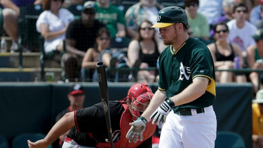 Oakland Athletics shortstop Jed Lowrie, right, reacts after striking out as Cincinnati Reds catcher Cory Miller looks on during the third inning of a spring exhibition baseball game in Phoenix, Tuesday, March 25, 2014. (AP Photo/Chris Carlson)
